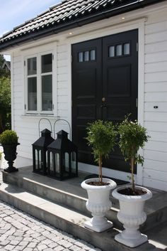 These oversized lanterns look great in front of this bijou cottage - play with scale.