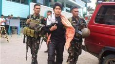 This photo taken on August 23, 2016 shows Philippine soldiers escorting Maute extremist group member Hassim Balawag Maute alias Apple Jehad to a military vehicle in Marawi City in the southern island of Mindanao