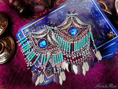 This exotic pair of clop-on chandelier earrings is made with antique silver third eye pendants decorated with Siam Red Swarovski rhinestones. The center of the eye is a vintage Amethyst glass faceted jewel. The beaded Czech glass strands are beautiful rich Periwinkle Purple and Garnet Red