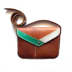 Leather purse made in cow hide in light brown and hand sewed with 100% polyester waxy thread. It has an additional pocket on its front divided in two