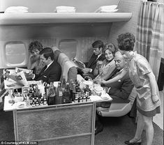 Passengers are served beverages by a flight attendant - with plenty of legroom - on a KLM ...