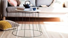The wire of a large light shade is used as the base for a coffee table for this DIY