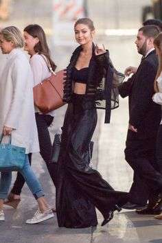 Gigi Hadid style: In a black bralette, sheer jacket, high-waisted wide-leg pants, heeled boots, gold hoop earrings and a black handbag while arriving at Jimmy Kimmel Live!.
