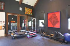 I love the big framed wooden mirrors against the black walls.  Bright artwork on the walls adds color to the dark room