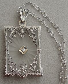An antique Art Deco 14k white gold and diamond camphor glass pendant from the 1930's.