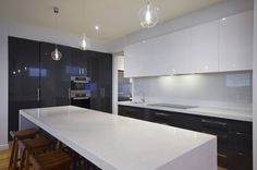 This modern kitchen oozes sophistication with its sleek black and white colour scheme. London Grey Caesarstone has been used for the benches with Polytec Onyx Fineline gloss for base cabinetry and Polytec Classic White Gloss for the overheads. A large pantry is hidden from view allowing for easy access to equipment and further space for preparation and storage.
