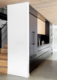 This modern black kitchen features an integrated fridge and freezer, an integrated stove top and an island to make preparing meals easy and convenient.