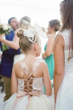 Adorable lace up ribbon flower girl dress: http://www.stylemepretty.com/destination-weddings/2015/11/21/elegant-white-wedding-in-greece-2/   Photography: Peter & Veronika - http://peterandveronika.com/language/en/