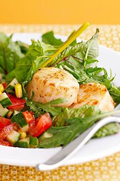 A nice option for a light lunch, these seared scallops are served with a fresh tomato, cucumber, and corn salad, and drizzled with a tasty basil vinaigrette. #salads #saladrecipes #healthysalads #saladideas #healthyrecipes