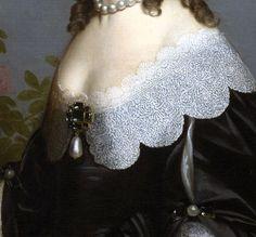 Particolare di opere: Elisabetta Stuart, regina di Boemia. Gerard van Honthorst, olio su tela del 1642. National Gallery, Londra. Un meraviglioso collo di pizzo smerlato scende sulle spalle dell'abito nero, fermata sul seno da una delle spille più viste del XVII, molto di moda con le pietre nere, l'oro e la perla a goccia che scende sotto: più in piccolo gli stessi materiali sono usati sul braccio per tenere fermo il taglio della manica.