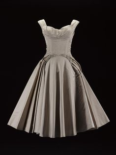 Woman's evening dress or ball gown, in pale beige silk taffeta, with a low sweetheart neckline with pleated detailing and wide shoulder straps, fitted, structured bodice with off-centre seams and padded bust and wide curving pleats to full stiffened skirt, three-quarter length, labelled in the centre back, the bodice of the dress is unlined, the skirt lined with stiffened paper: American, by Ceil Chapman, mid 1950s  Museum reference K.2013.80