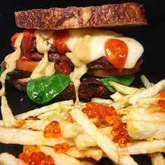 """Tejano"" burger. Angus beef patty, red heirloom tomatoes, baby spinach, shredded red onion, melted mozzarella. Smothered in ketchup and a guava-chipotle BBQ sauce. Held together by two thick slices of toasted country bread. Side of roe-topped French fries."