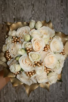 Bridal Bouquet: Vendela roses, ivory spray roses, gold holly berries (individually wired and clustered), and British ivy sprayed gold.
