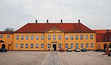 Roskilde Mansion (Danish: Det Gule Palæ i Roskilde), also known as Roskilde Palace and as the Yellow Mansion (Danish: Det Gule Palæ), is a former royal Baroque mansion in central Roskilde, Denmark. Located just east of Roskilde Cathedral, it now houses both an exhibition veneue for contemporary art and the office and official residence of the Bishop of Roskilde.