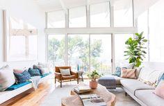 Decoração de casa branca com transparência e plantas. Escada branca, corrimão branco, piso de madeira, sofá, mesa de centro de madeira e luz natural.