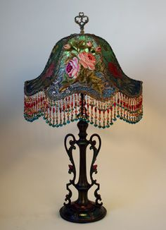 Lovely Art Nouveau 1920s lamp base holds an emerald green and teal silk Gish lampshade. The shade is covered in antique Spanish net lace, heavy coppery metallic lace and an antique embroidered appliqué of roses adorn the front panel. Hand beaded glass fringe embellishes the lamp.