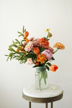 cute arrangement of flowers in fall shades of orange, pink and yellow.