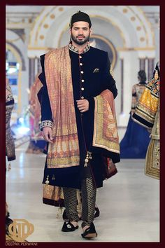 A black hand embroidered sherwani with work on the neck with kora, dabka & stones. Paired with a banarsi churidar & a gold screen printed shawl