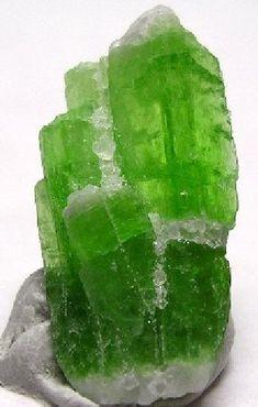 Kyanite: Al2SiO5 = Al[6]Al[6]OSiO4  Comments:Cluster of 4, green, gemmy, fluorescent blades of kyanite.  Location:Pech, Afghanistan.  Scale:1.7 x 1.0 x 0.3 cm.  Copyright:© Kieth Hayes