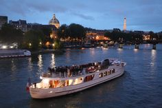 Those people cruising down the river Seine at night sure look like they're enjoying Paris!