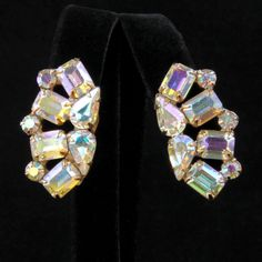 Spectacularly sparkly clip earrings have four emerald-cut rhinestones alternating with three small chatons, gracefully curving around two teardrops. All the stones flash with iridescent aurora boreali