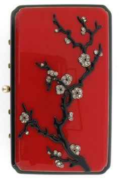 A French Art Deco gold minaudiere. The cover decorated with black enamel prunus tree with diamond blossom. On red enamel ground within black enamel border. With similar enamel decoration to the base. Pearl thumb piece, the interior with lipstick and assorted compartments. The mirror section opens to reveal and aide memoir and the spring hinged clip with pieced blossom decoration. The lozenge shaped makers mark EC and fish between. And various French controll marks.