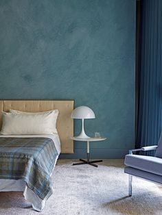 This master bedrooms walls are wrapped in a blue-green plaster | archdigest.com