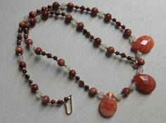 18 inch strand featuring faceted teardrops of red brecciated jasper, goldstone beads, moonstone beads, red agate beads, copper bicone crystals,