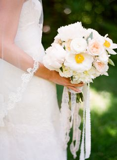 Beautiful lace hanging from the bouquet!  You could attach a piece of beautiful jewelry/cameo as well to the handle.
