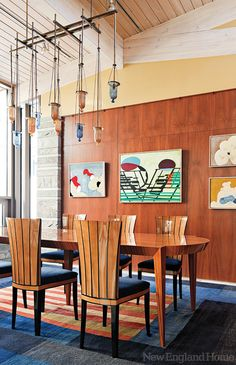 The colors in the dining room's rug play off the wood wall and artwork, the blue chair cushions and light fixture.