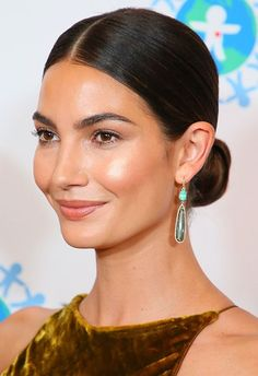 Bun 3.0 comes in the shape of a sleek, low number fit for the red carpet (or IRL, date night). Nail it by creating a centre parting (Lily Aldridge's hair happy place), and gathering at the nap of your neck. Tie into a neat bun with a hair-coloured tie then tidy any rogue fly aways by spritzing hair spray to a brush and combing back towards your bun. Finish with red lippie and glitzy earrings for va-va-voom feels