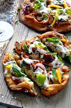 Tandoori Chicken Naan Pizzas. These grilled pizzas feature juicy tandoori chicken, mango, mozzarella, mint, cilantro, and yogurt. Premade naan make a great base for a delicious pizza dinner with Indian flair.   http://hostthetoast.com