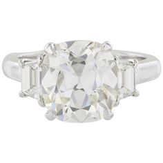 4.14 Carat GIA Cert Cushion Cut Diamond Platinum Three Stone Ring | From a unique collection of vintage three-stone rings at https://www.1stdibs.com/jewelry/rings/three-stone-rings/