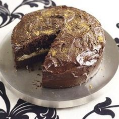An earl grey chocolate cake on a silver plinth decorated in golden glitter sugar