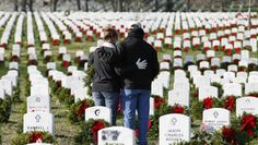 Volunteers pauses over the grave of a fallen soldier after laying a holiday wreaths, during Wreaths Across America Day at Arlington Cemetery