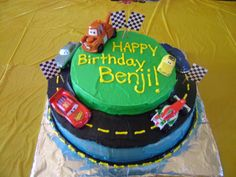 Cars Cake!  Super easy!  Two different sizes of circle cakes, black frosting for the road, printed checker flags off the computer and put on tooth picks, and used his toy cars!  Easy!