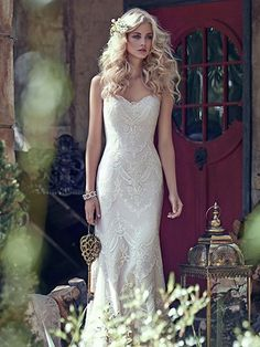 Maggie Sottero - KIRSTIE, Elegant lace appliqués drift atop tulle to create this breathtaking bohemian sheath wedding dress, with a timeless, romantic sweetheart neckline. Finished with covered buttons over zipper and inner corset closure.