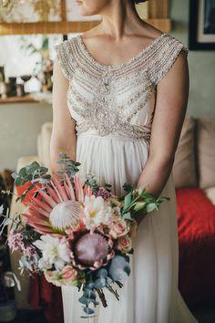 Romantic Anna Campbell beaded wedding dress and Protea bouquet | iZO Photography | See more: http://theweddingplaybook.com/romantic-australian-bush-wedding/