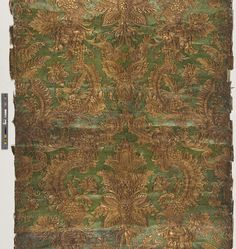 Unused wallpaper sample of Japanese leather paper. Baroque style pattern with large flowers and foliate c-scrolls and openwork. Pebble embossed background. Relief detail in gold wash and background is stenciled in green on a gilt ground.