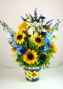 Sunflower Silk Floral Arrangement #16681  This silk floral arrangement is bursting with a plethora of bright sunflowers, light blue delphinia and white larkspur, royal blue poms, bright yellow mums, full and lush greenery and blue and yellow accent sprays. The ceramic container has a royal blue background with painted pictures of sunflowers. Dimensions for this abundant silk flower arrangement are 27 inches high and 22 inches wide.