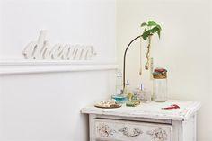 """Una casa con estilo vintage moderno  . La mesa provenzal reciclada que ubicó en el rincón ($890 c/u, La Florinda) y la mesita de luz reciclada son casi los únicos muebles. El cartel """"dream"""" ($150, La Florinda) da la orden, que se cumple a rajatabla sobre la manta verde hindú, regalo de una amiga.  /Javier Picerno"""
