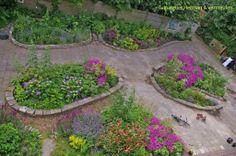 De tegels van het voormalige schoolplein zijn gebruikt om eilanden te maken die elk hun eigen karakter hebben. Op die manier ontstaan paadjes en pleintjes tussen de bloemen.