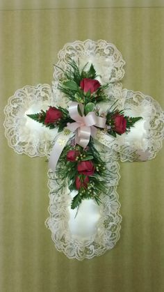 Sympathy piece. A silk cross with spray roses and scrip added to a ribbon. Just right for that special loved one.