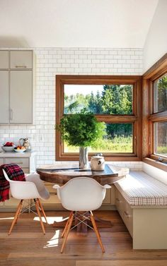 built-in dining nook with white subway tile and wood windows