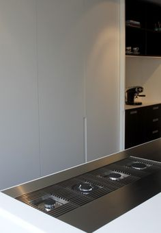 Stainless steel integated hobs in white minimal kitchen by Remmelt Amsterdam