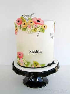 This beautiful, sweetly designed cake features hand-painted flowers on fondant, cut out like a paper collage and applied to a simple white fondant cake. Black and white drawings of birds and branches sparingly pepper the cake for a simple minimalist-meets-craft design.