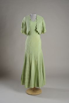 Date Made: 1932  Description:  Dress; light green crepe, bias cut with top stitched chevron seaming, matching short sleeves bolero-style jacket with sawtooth edge (B). Dress (A), double V-neck with deeper V in front.