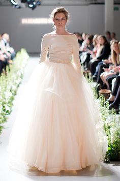 This blush Elizabeth Stuart wedding dress features an off the shoulder top and a tulle skirt.