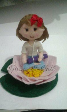 Boneca fazendo yoga dentro de uma flor de lótus confeccionada em feltro