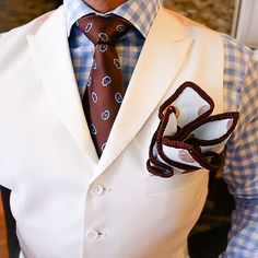 light blue gingham shirt. cream waist coat. burgundy and blue patterned tie. white pocket square w/burgundy trim. crisp. clean. fresh. style.